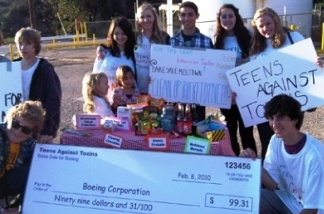 Students display a check they tried to give to Boeing -- the proceeds from their bake sale.