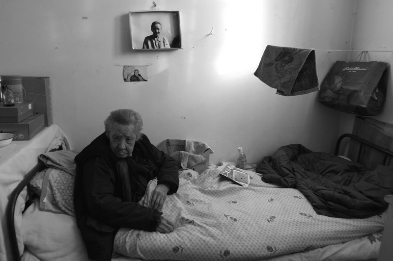 A 104 year old woman rests on her nursing home bed, under the watchful gaze of her younger self.