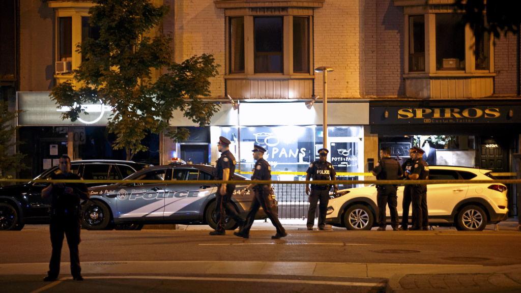 Police officers walk the scene  in the Greektown neighborhood of Toronto Sunday night. Police say a gunman opened fire on 14 people in a restaurant. Two people are dead including the gunman, police reported.