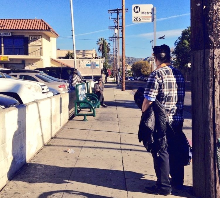 A man stands in the shadow cast by an electric pole as he waits for the bus at a stop with no bus shelter. Less than a quarter of L.A. bus stops have shelters and a city plan to add more has fallen apart.