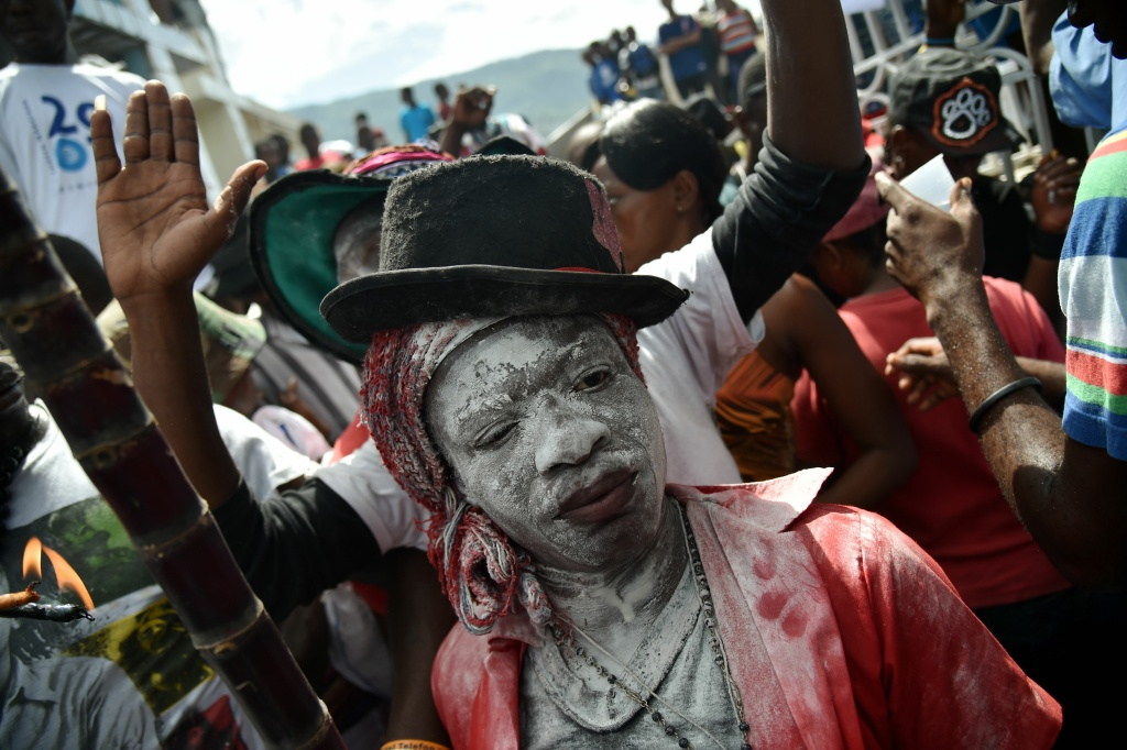 A devotee pretending to be the spirit known as a Gede smiles during a ceremony honoring the Haitian voodoo spirits of Baron Samdi and Gede on the Day of the Dead in the National Cemetery in Port-au-Prince, Haiti on November 1, 2016.