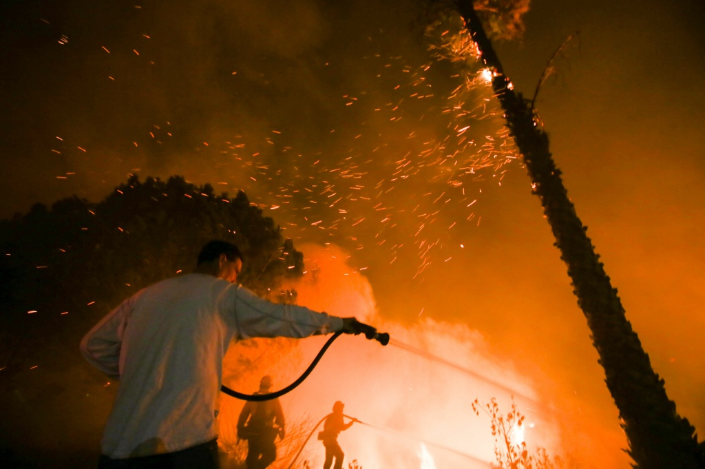 A man waters his home as firefighters battle a wildfire as it burns along a hillside near homes in Santa Paula, California, on December 5, 2017.