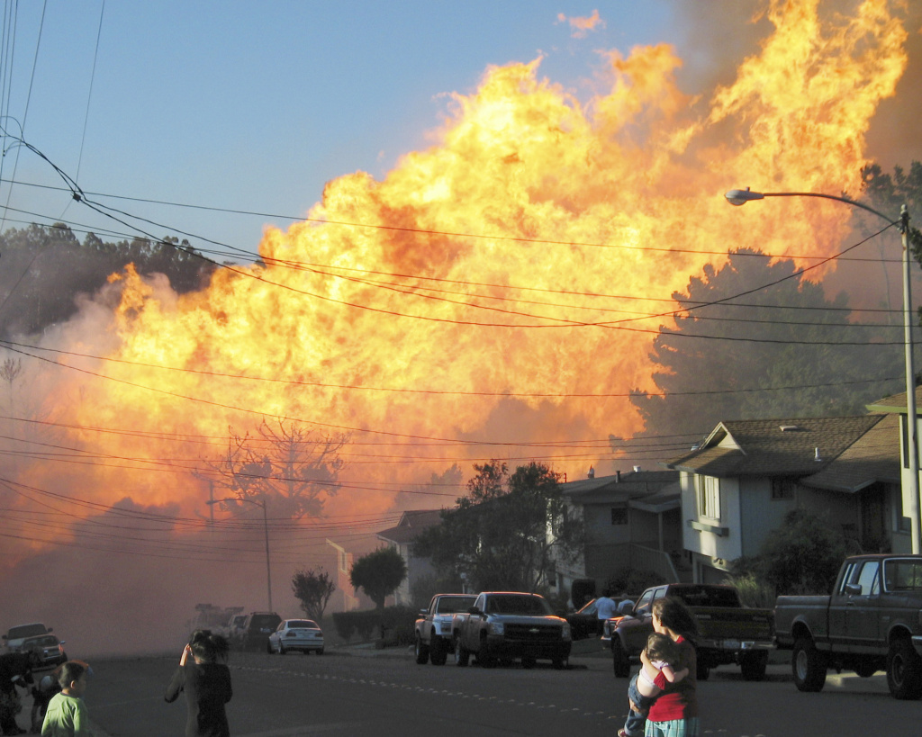 In this Sept. 9, 2010, file photo, a massive fire roars through a mostly residential neighborhood in San Bruno, Calif. A blast of a Pacific Gas & Electric Co. natural gas pipeline in San Bruno sent a giant plume of fire into the air, killing eight people and destroying 38 homes. The company is set to face a jury in a criminal trial starting Thursday.