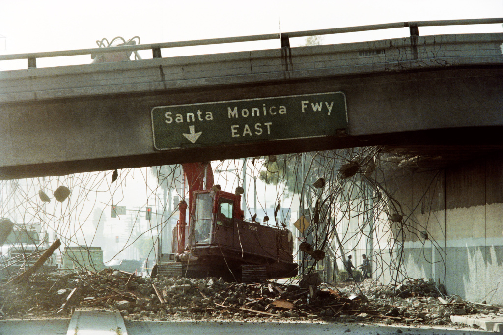 A picture taken on January 19, 1994 in Los Angeles, California, shows a bulldozer tearing down a section of the Santa Monica Freeway that collapsed during the Northridge earthquake.