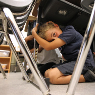 "SAN FRANCISCO, CA - OCTOBER 20:  Third grade students at William L. Cobb Elementary School take cover under desks as they participate in the ""Great California ShakeOut"" earthquake drill on October 20, 2011 in San Francisco, California.  An estimated 8 million Californians will take place in the fourth annual Great California ShakeOut earthquake drill which will help educate residents prepare for a major earthquake.  (Photo by Justin Sullivan/Getty Images)"