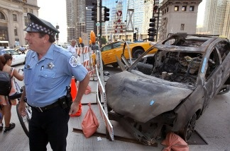 A Chicago police officer stands guard in front of a staged car accident during the filming of the movie Transformers 3, in the