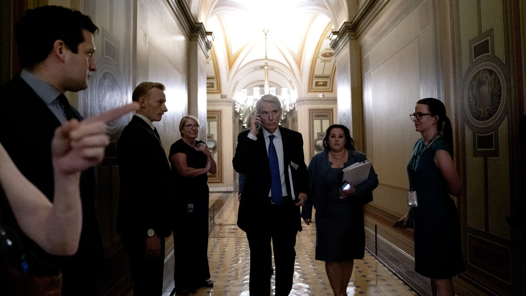 Sen. Rob Portman, R-Ohio, center, arrives to a bipartisan infrastructure meeting at the U.S. Capitol on Wednesday.