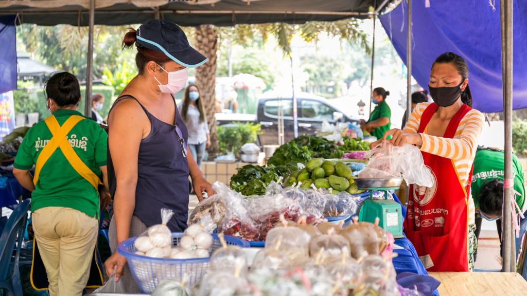 A shopper buys vegetables last month in Vientiane, Laos. The government announced that some offices and businesses will resume normal operations on Monday. The country has confirmed 19 COVID-19 cases and no deaths.<em></em><a href=
