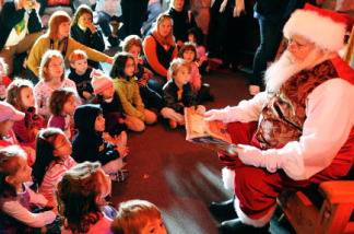 Santa Claus student Tom Carmendy, of Westminster, Colorado dresses up as Santa Claus and reads a Christmas story for a group of elementary school children during the Charles W. Howard Santa Claus School workshop on October 17, 2008 in Midland, Michigan.