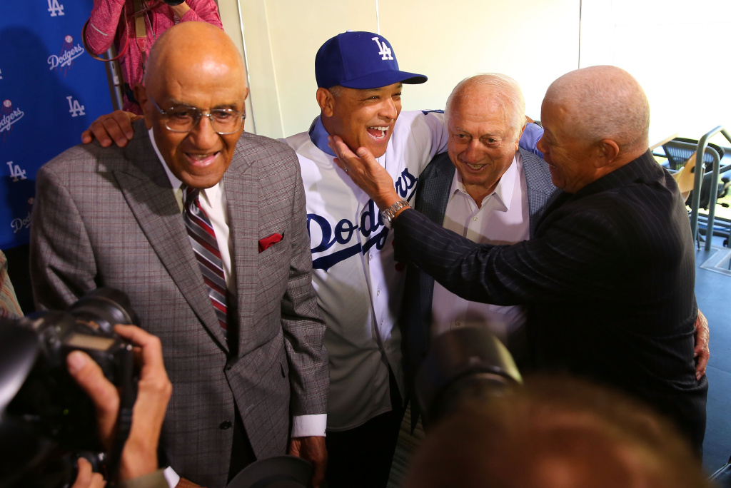 Former Dodgers player Maury Wills, right, congratulates Dave Roberts on his position as the new Los Angeles Dodgers manager as former Dodgers player Don Newcombe, left, and former Dodgers manager Tommy Lasorda, second from right, look on at Dodger Stadium on December 1, 2015 in Los Angeles, California.