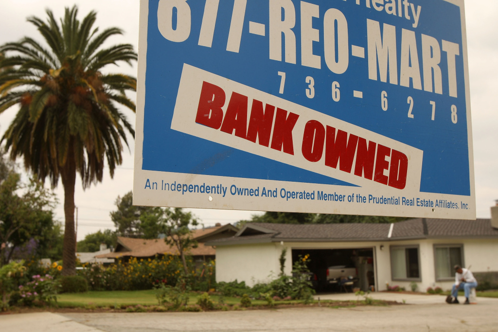 A realtor sign advertises a bank-owned house for sale in Pasadena.