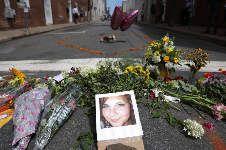 Flowers surround a photo of 32-year-old Heather Heyer, who was killed when a car plowed into a crowd of people protesting against the white supremacist Unite the Right rally on August 13, 2017 in Charlottesville, Virginia.