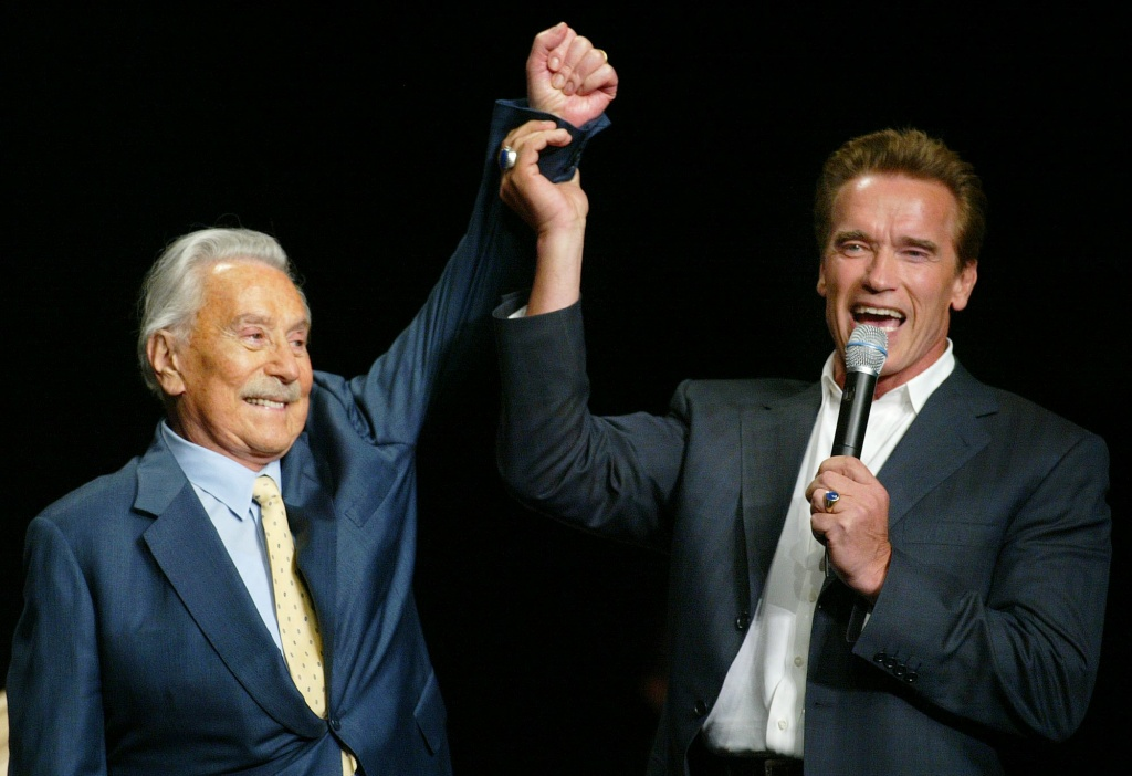 Arnold Schwarzenegger, right, raises the arm of Joe Weider, the creator of Mr. Olympia Bodybuilding competition, during the 39th annual Mr. Olympia event Saturday, Oct. 25, 2003, at The Mandalay Bay Hotel & Casino in Las Vegas.