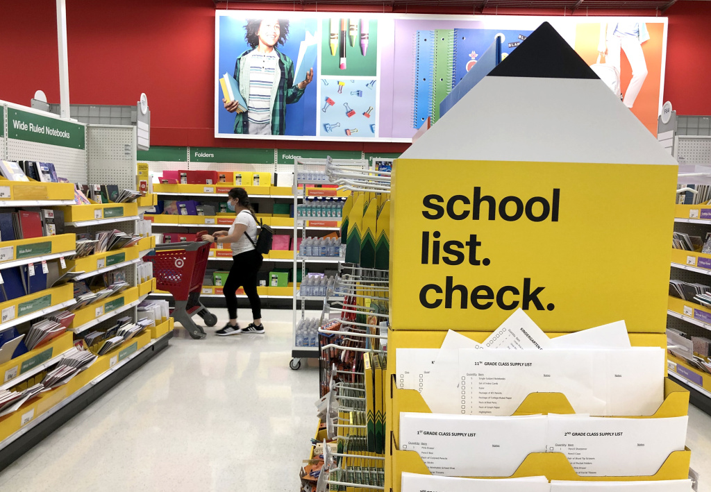 A shopper walks past shelves of school supplies at a Target store in San Rafael, Calif. Preparing for both in-person and virtual learning has families budgeting for new school supplies and bigger purchases.
