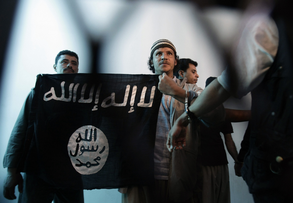 In this April 23, 2013 file photo, a suspected Yemeni al-Qaida militant, center, holds an Islamist banner as he stands behind bars during a court hearing in state security court in Sanaa, Yemen. A top leader of Yemen's al-Qaida branch has claimed responsibility for last week's attack on a Paris newspaper when two masked gunmen killed 12 people, including much of the weekly's editorial staff and two police officers. Nasr al-Ansi, a top commander of Al-Qaida in the Arabian Peninsula, or AQAP as the branch is known, appeared in an 11-minute Internet video posted Wednesday, Jan. 14, 2015.