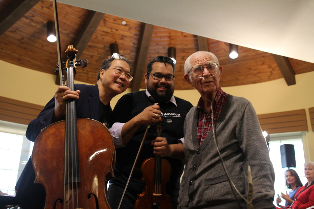 Yo-Yo Ma and Vijay Gupta pose with a resident of Valencia Terrace, an assisted living facility for seniors.