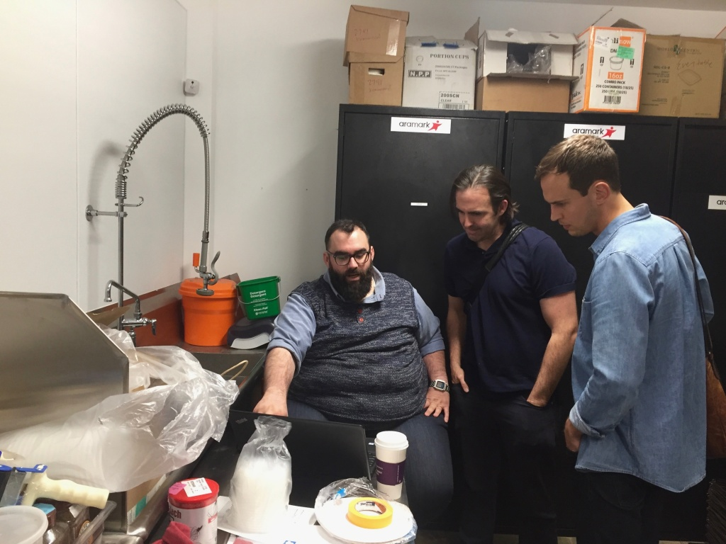 Everytable co-founders Sam Polk (middle) and David Foster (right) talk about the packing process with a chef in Everytable's commercial kitchen in South L.A.