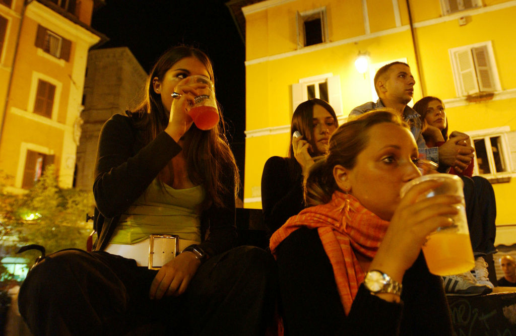 Virginia Recchi, 16, Violante Pasolini, 17, (front C) and Ludovica Lombardini, 17, sit as they have a drink in a square June 17, 2004 in Rome, Italy.