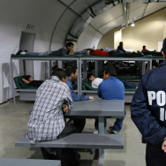 An Immigration and Customs Enforcement (ICE) officer guards a group of 116 Salvadorean immigrants that wait to be deported,at Willacy Detention facility in Raymondville, Texas.