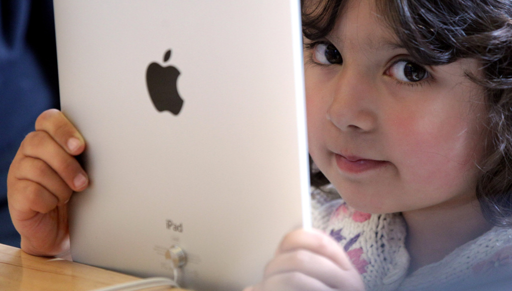 A young girl holds an Apple iPad on display.