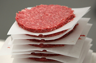 A stack of ground beef patties moves on a conveyor belt at a meat packing and distribution facility June 24, 2008 in San Francisco, California.