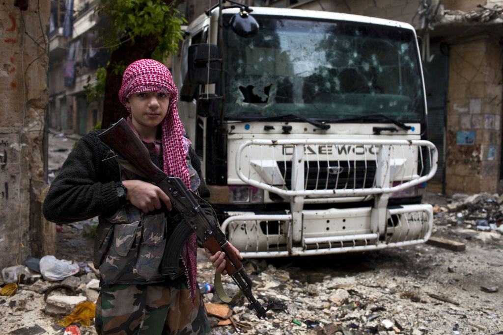 A Syrian rebel poses next to a checkpoint in the Salahadine district of Aleppo on December 20, 2012.
