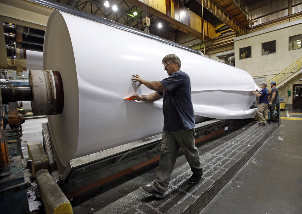 In this Monday, Nov. 10, 2014, file photo, workers cut a sample section off a large roll of paper made at the Sappi Paper Mill in Skowhegan, Maine. Not only are U.S. paper companies facing precipitous drops in demand, but they're also confronting tough competition from China, the country that invented paper 2,000 years ago. Still, some industry niches are surprisingly robust.