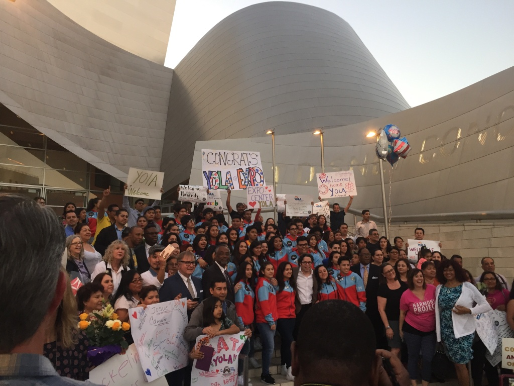 YOLA students and families pose for a group photo on the steps of Disney Hall. LA Philharmonic music director Gustavo Dudamel is in the center of the front row.