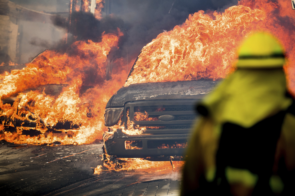 Flames consume vehicles as a wildfire rages in Ventura on Tuesday, Dec. 5, 2017.