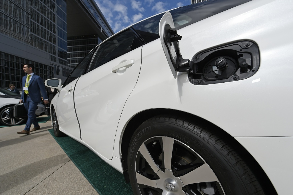 An attendee walks past the hydrogen fuel cell Toyota Mirai, at Drive The Dream 2015, an event aimed at accelerating the continued adoption of plug-in electric vehicles in California.