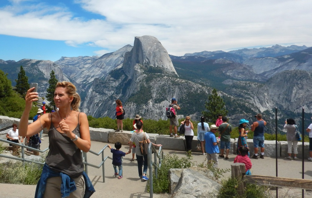 This August 5, 2015 photo shows a woman taking a selfie atop Glacier Point with a background view of Half Dome at Yosemite National Park.
