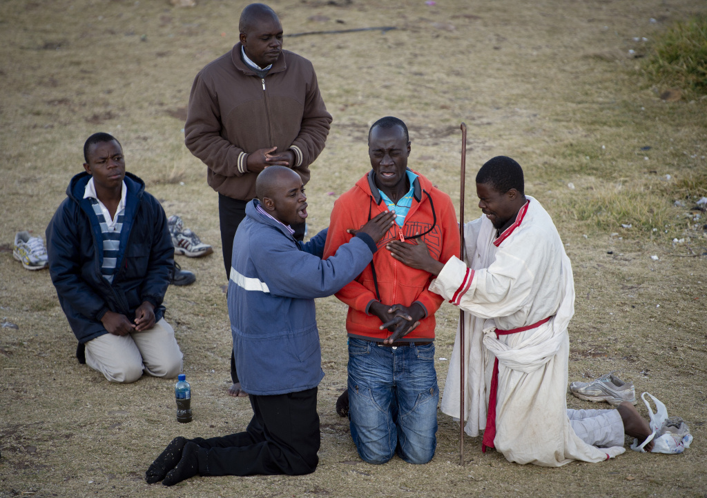 Worshippers from a Baptist church perform exorcism on a congregation member in the Hillbrow neighborhood overlooking Johannesburg, South Africa on June 30, 2013.
