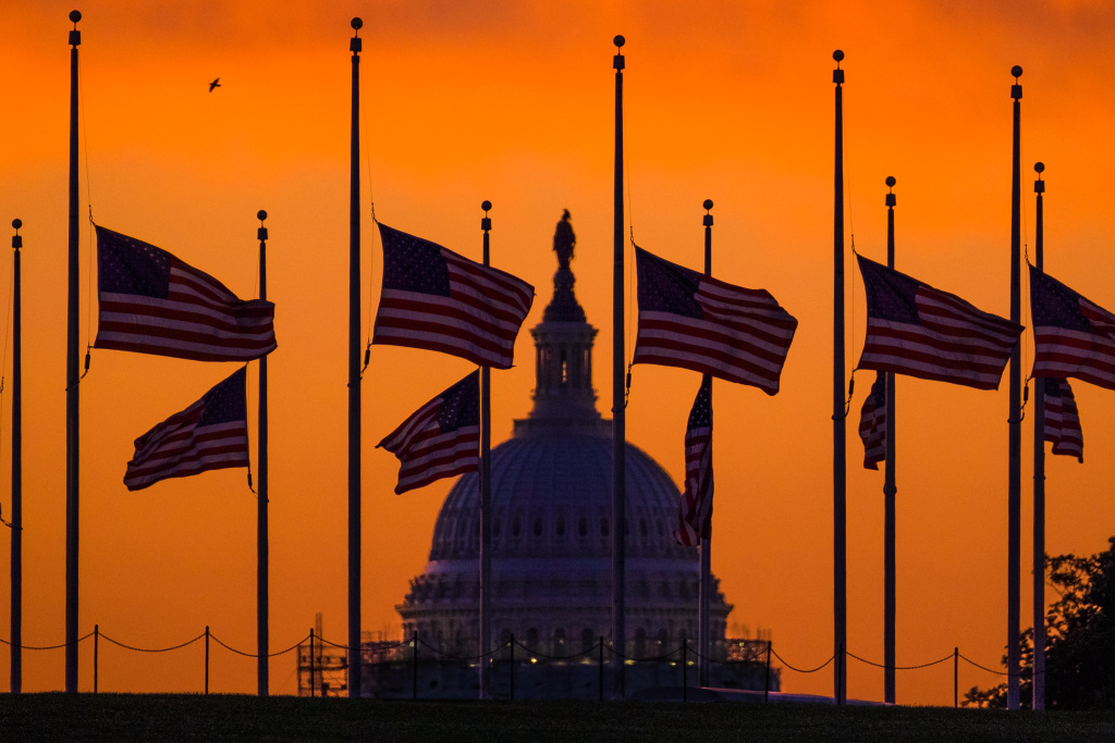 Flags fly at half-staff around the Washington Monument at daybreak in Washington with the US Capitol in the background Monday, June 13, 2016. President Barack Obama ordered flags lowered to half-staff to honor the victims of the Orlando nightclub shootings.