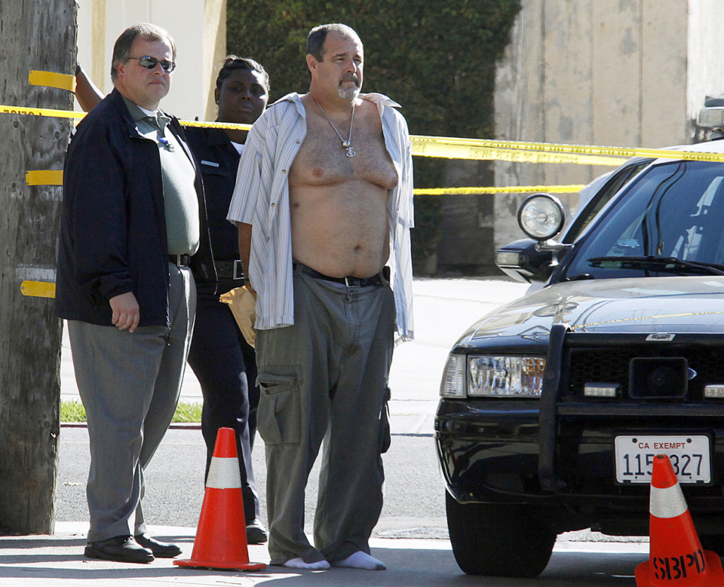 Police officers stand with Scott Evans Dekraai (with open shirt) near the Salon Meritage beauty salon in Seal Beach, Calif. on Wednesday, Oct. 12, 2011. Dekraai, accused of killing eight people, faces a March 24, 2014 trial. (File photo)