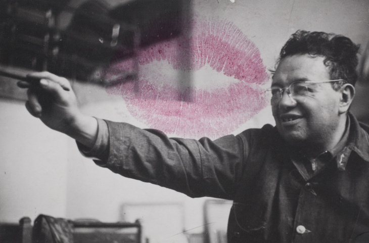 A photo of Diego Rivera, with a kiss from Frida Kahlo