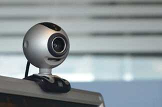 A web cam perched on top of a computer.