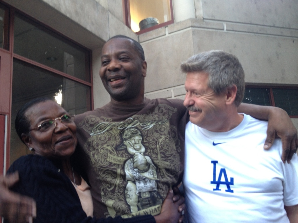 File: Wilma Register, Kash Delano Register and former inmate Keith Chandler hug. Chandler was instrumental in helping Register with his legal appeals.