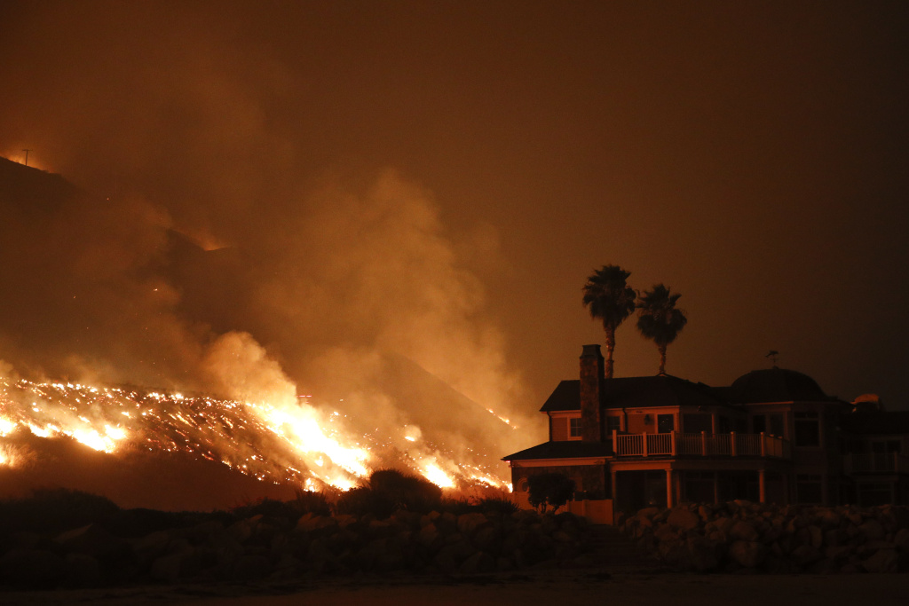 A wildfire threatens homes as it burns along the 101 freeway on Tuesday, Dec. 5, 2017 in Ventura, California. Fueled by ferocious Santa Ana winds, the fire burned a psychiatric hospital and scores of homes and other structures.