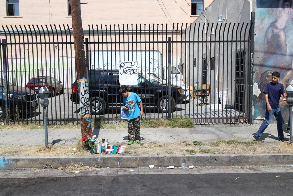 A boy stands over the memorial for 14-year-old Jesse Romero, who was shot and killed by police in Boyle Heights on Aug. 9.