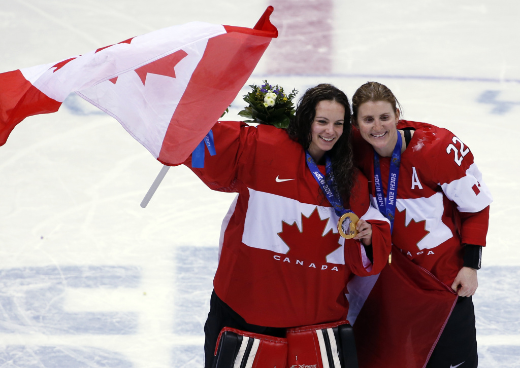 Goalkeeper Shannon Szabados of Canada (1) and Hayley Wickenheiser of Canada (22) celebrate after the medal ceremony in the women's ice hockey tournament at the 2014 Winter Olympics, Friday, Feb. 21, 2014, in Sochi, Russia. Canada won gold after defeated Team USA 3-2 in overtime.