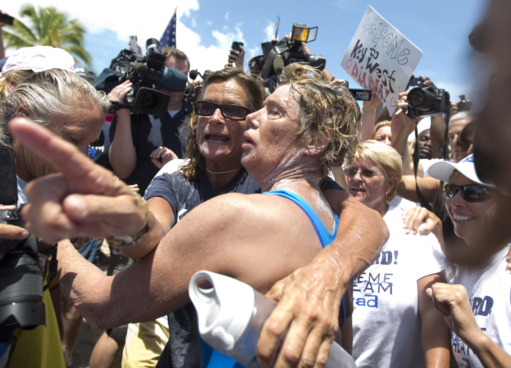Endurance swimmer Diana Nyad, right, and her trainer, Bonnie Stoll hug after Nyad walks ashore Monday, Sept. 2, 2013 in Key West, Fla. after swimming from Cuba. Nyad became the first person to swim from Cuba to Florida without the help of a shark cage. She arrived at the beach just before 2 p.m. EDT, about 53 hours after she began her swim in Havana on Saturday.  (AP Photo/J Pat Carter)