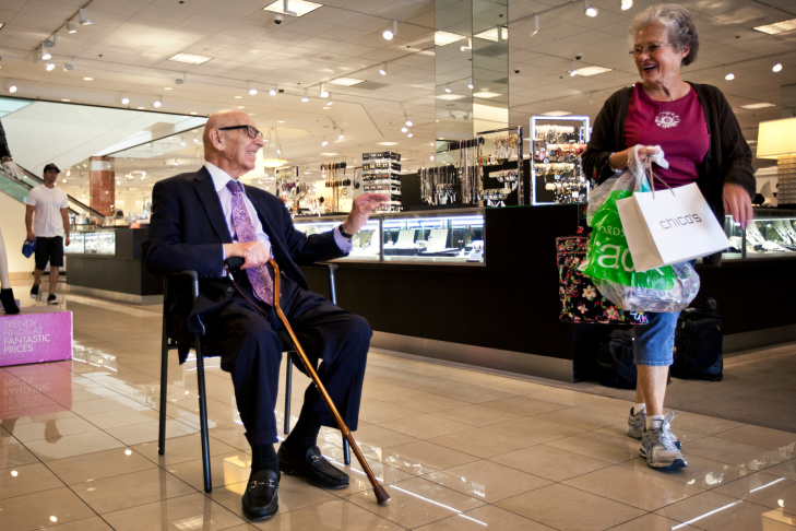 Ted DiNunzio high-fives 2-year-old Zoey at the Nordstrom store in Arcadia on Sept. 20. DeNunzio works at the store as a greeter every Friday and Saturday.