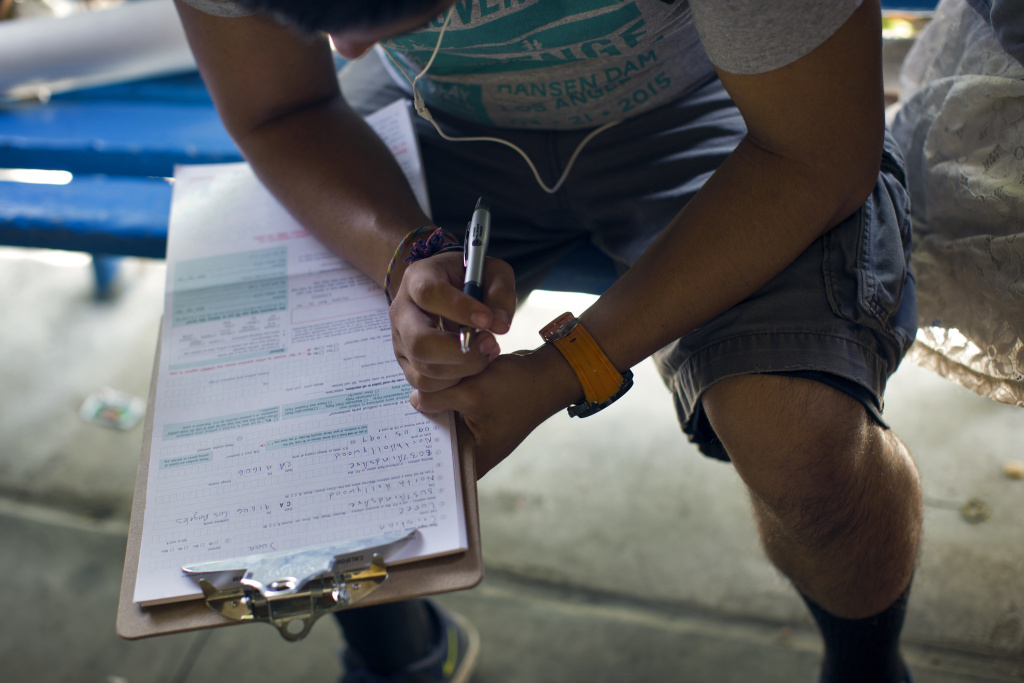 FILE: A student at North Hollywood High School fills out a voter registration form during lunch on Thursday, April 30, 2015, as part of a student voter drive.