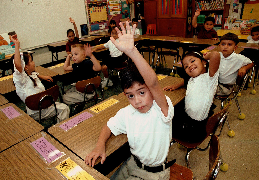 FILE - Monolingual Hispanic students raise their hands to answer a question during a class taught in Spanish in Tyler, Texas.