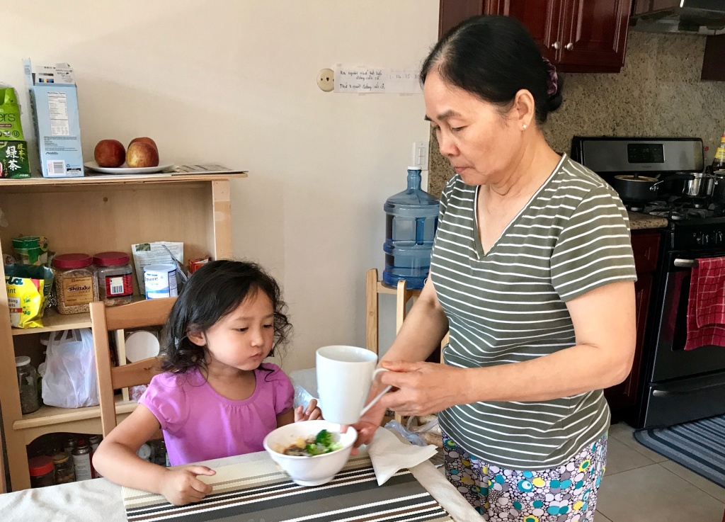 Manh Vo feeds her granddaughter Madison, 4, an after-school snack. Vo, who speaks Vietnamese, said communication with her granddaughter has improved since Madison began the Vietnamese dual language immersion program at Murdy Elementary School, Sept. 19, 2017.