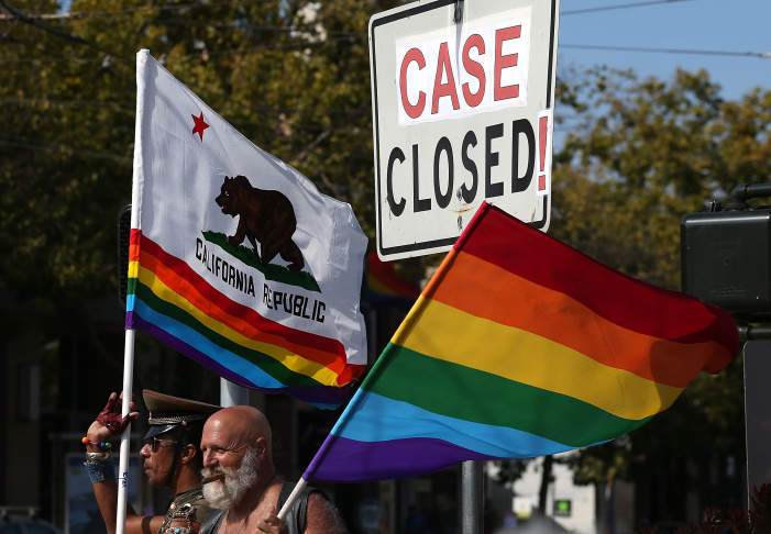 Same-sex marriage supporters hold pride flags next to an altered street sign that reads