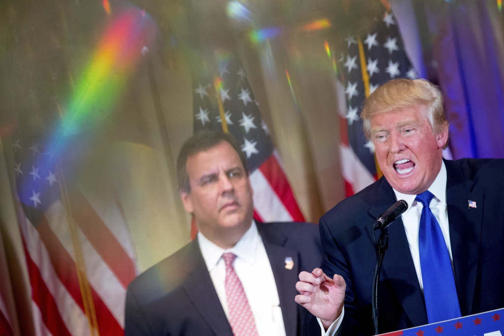 Republican presidential candidate Donald Trump, accompanied by New Jersey Gov. Chris Christie, left, and seen through a chandelier, speaks during a news conference on Super Tuesday primary election night in the White and Gold Ballroom at The Mar-A-Lago Club in Palm Beach, Fla., Tuesday, March 1, 2016. (AP Photo/Andrew Harnik)