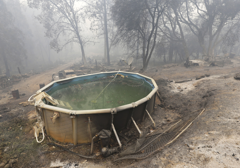 A swimming pool is covered with ash and debris from the Butte Fire, Saturday, Sept. 12, 2015, that destroyed a nearby home in Mountain Ranch, Calif.  (AP Photo/Rich Pedroncelli)