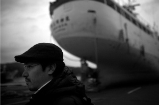 Ship owner Yuta Suzuki and one of his grounded vessels that was thrown on shore during the tsunami in Kesennuma, Miyagi prefecture.