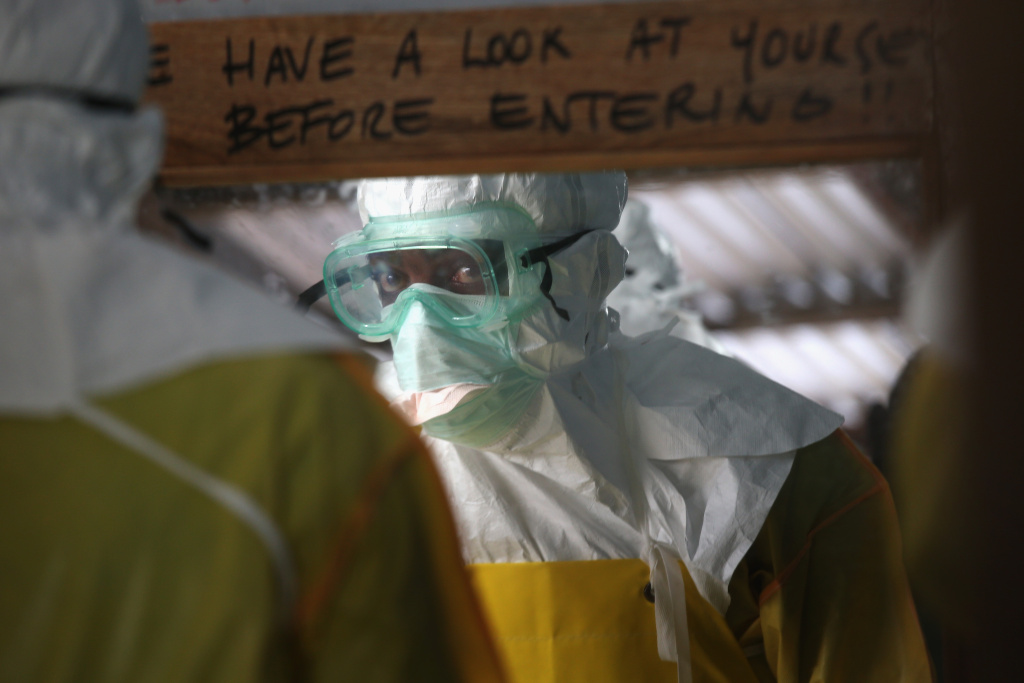 A staffer for Doctors Without Borders (MSF), suits up in protective clothing before entering a high-risk area of the MSF Ebola treatment center on August 21, 2014 near Monrovia, Liberia.
